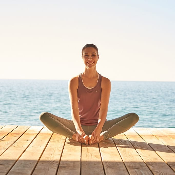 Smiling woman practicing yoga on a boardwalk